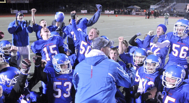CLASS D FOOTBALL:Oak Hill High School head football coach Stacen Doucette, celebrates with his team after defeating Bucksport High School 42-35 for the Class D championship at Fitzpatrick Stadium in Portland on Saturday.