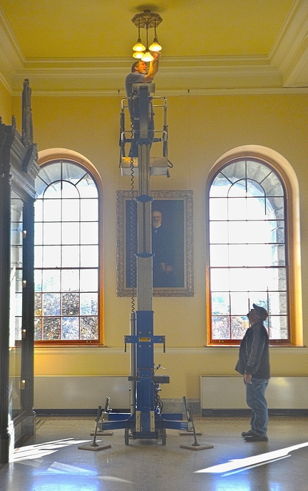 Mike Mahoney, top, works on a lift as Derek Nickerson stands by on Thursday in front a portrait of James G. Blaine at the State House in Augusta. The Bureau of General Services employees had several other hard to reach bulbs to replace in the second floor Hall of Flags.