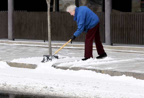 FIRST SNOW: The first snow fell on central Maine on Tuesday, bringing out snow shovels, plows and worry for road conditions. Gerald Giroux did his part to clear sidewalks in front of Berry's Stationers on Main Street in Waterville.