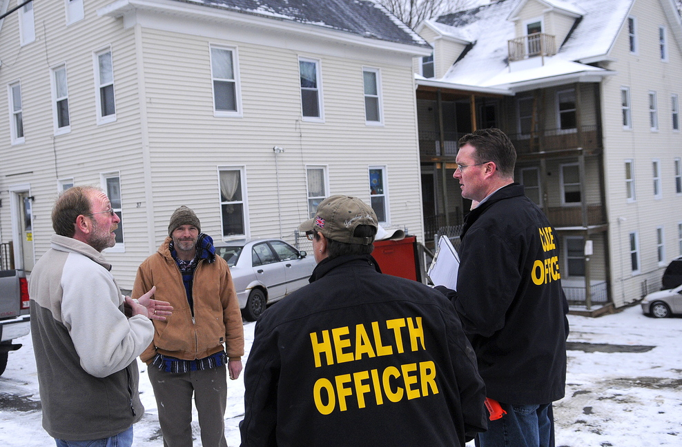 INSPECTION: Property maintenance manager Jim Dutil speaks with city and state officials Tuesday after an inspection of the apartment building at 37 Washington St. in Augusta, owned by Jim Pepin. The city of Augusta got an administrative search warrant last week to enter and inspect several of Pepin's multi-unit properties.