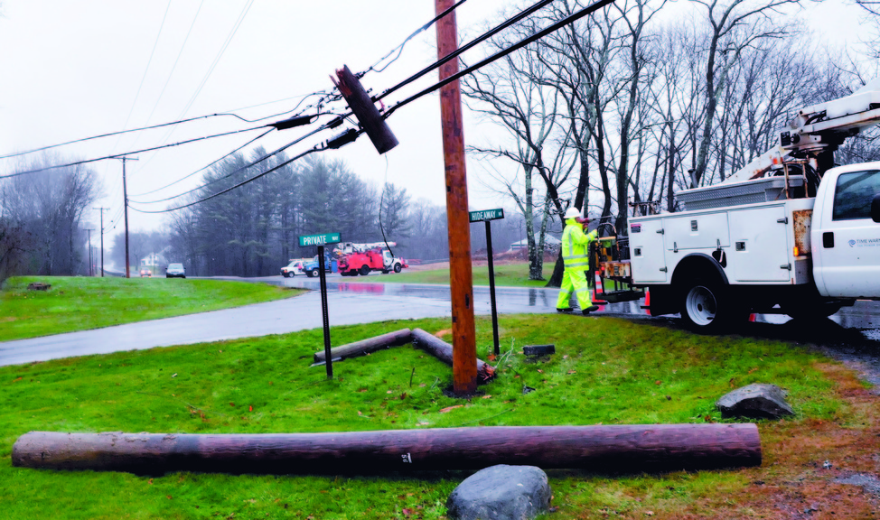 DOWN AND OUT: A Time-Warner company employee prepares to reconnect service to a new utility pole after the pole on ground was broken when a wind-blown tree toppled onto a nearby wire along U.S. Route 202 in Unity on Wednesday. Crews from Unitel and Central Maine Power worked to restore their services after the pole came down about 10:30 a.m. and were finished around 1:45 p.m. Traffic was re-routed around the scene.