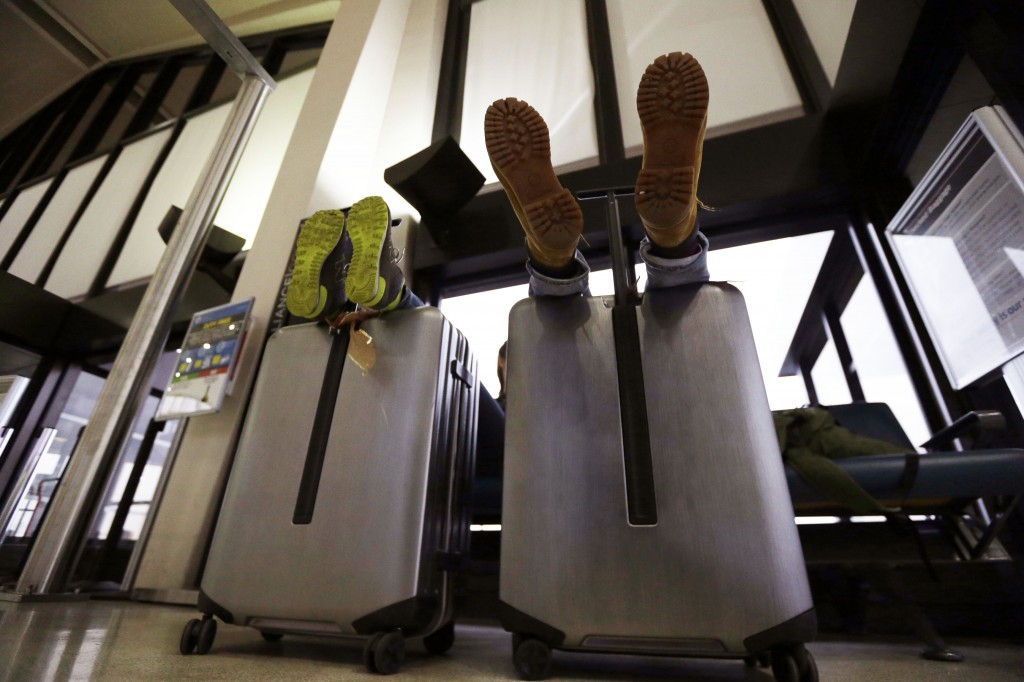 A couple rest their feet on their luggage while waiting for their flight to return home to Germany at Newark Liberty International Airport on Wednesday in Newark, N.J. East Coast travel delays didn't cause a major ripple effect for the rest of the nation.