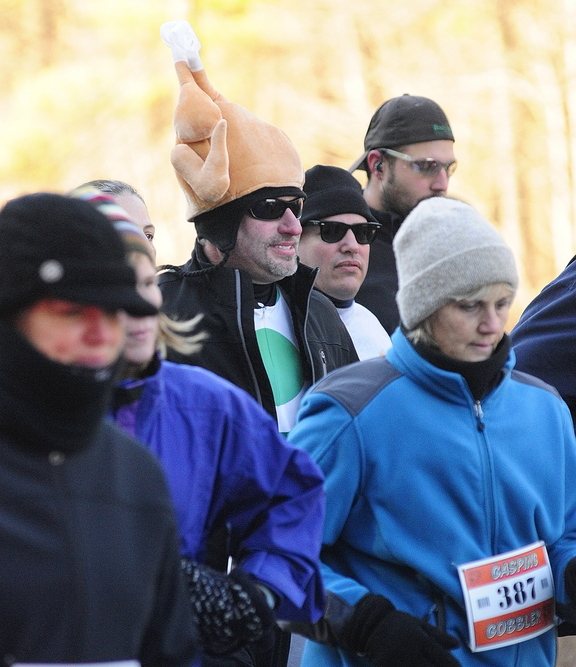 IT'S COLD: Runners area bundled up against the cold at the start of the Gasping Gobbler 5k run which began and finished at Cony High on Thursday November 28, 2013 in Augusta. There were over 400 registrants in the event that gave turkeys and other Thanksgiving dinner groceries as prizes.