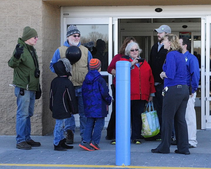 PROTEST: Priscilla Jenkins, of Moveon.org, in red, fourth from right, reads aloud a statement to several Walmart employees, right, during a Black Friday protest outside the Walmart Supercenter in Augusta. Jenkins, also a Winthrop town councilor, swore at the employees as they were asking her group to leave the premises.