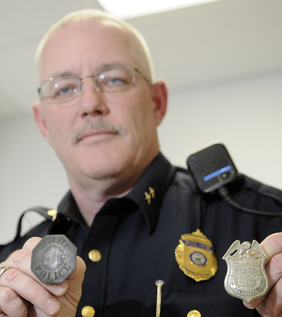 THE BEAT GOES ON: Augusta Police Chief Robert Gregoire holds two badges that belonged to Elbridge Pedder, a Civil War veteran who patrolled the city in the late 19th century. Augusta Police officers are attempting to recover the history of the agency.