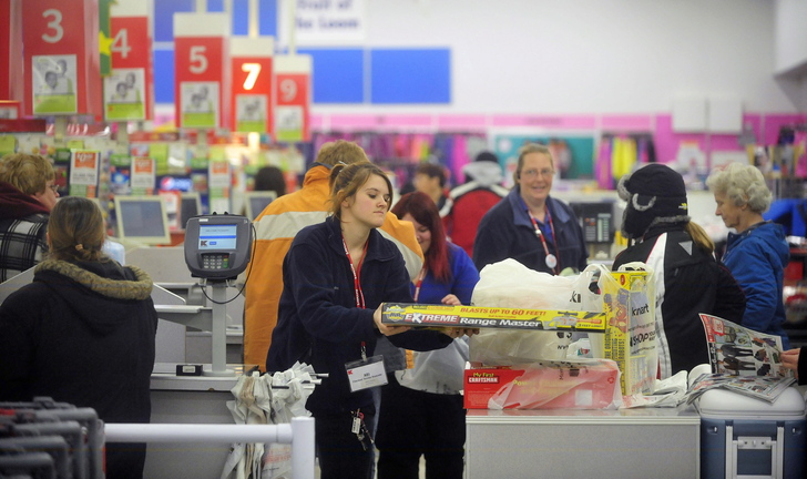 BLACK FRIDAY: Abi Hewins, a cashier at Kmart, checks out customers on Black Friday at Kmart on upper Main Street in Waterville.