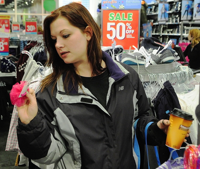 BLACK FRIDAY: A pair of shoppers walks past advertisements offering 50 percent off discounts during early morning Black Friday shopping at 6:15 a.m. Friday in Augusta.
