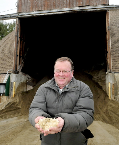 Staff photo by David Leaming PASS THE SALT: Skowhegan Road Commissioner Greg Dore holds a handful of some of the salt that is mixed with sand at the town sand shed. Dore said without the use of salt the roads would be more dangerous for drivers and expensive for the town to maintain roadways.