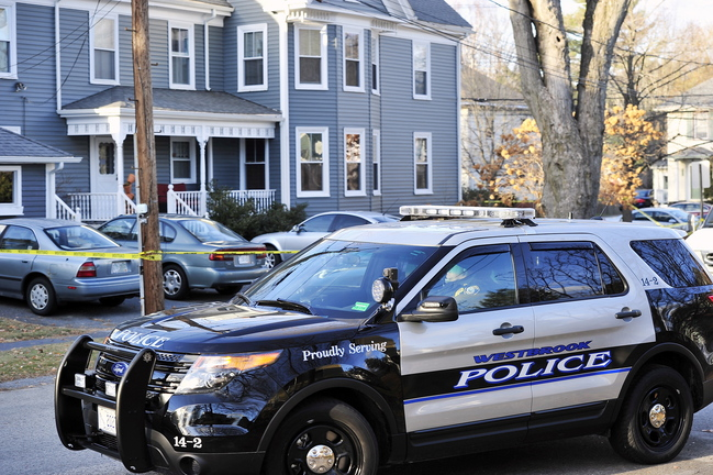 A Westbrook police officer parks his sport utility vehicle to block traffic on Waltham Street in Westbrook as state police investigated an apparent domestic-violence slaying and suicide Saturday. The violence left two men dead.