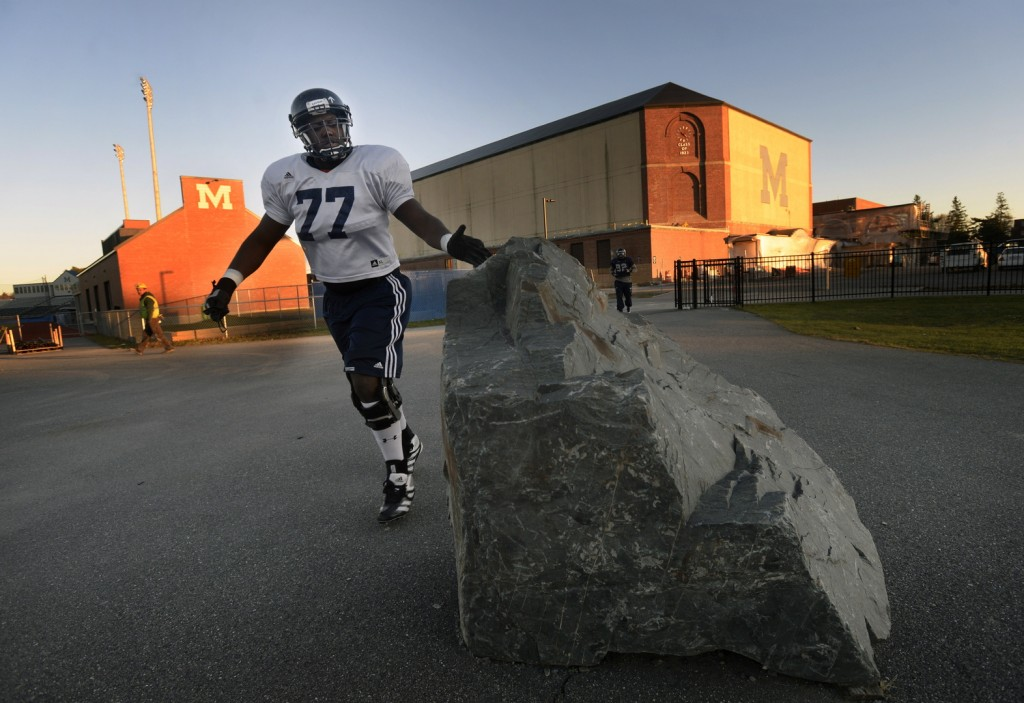 "TOUCH THE ROCK: University of Maine football player Isaiah Brooks touches the rock at the entrance of Harold Alfond Sports Stadium in Orono before practice Wednesday. The rock has an upward pointing arrow painted on it, which signifies the Black Bears motto ""One Direction."""