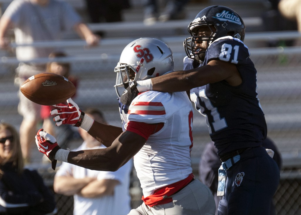 Maine receiver Jordan Dunn has his hands full in keeping Stony Brook defensive back Winston Longdon from intercepting a pass in the first half Saturday at Orono.