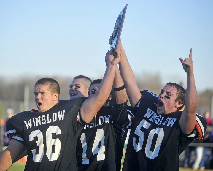 Staff photo by Michael G. Seamans Winslow High School teammates Zach Guptill, 36, left, Troy Ellis, 79, back left center, Matt Fortier, 14, right center, and Tanner Gillliland, 50, right, hold up the Eastern Class C championship plaque after defeating Waterville Senior High School 49-12 in Winslow on Saturday.
