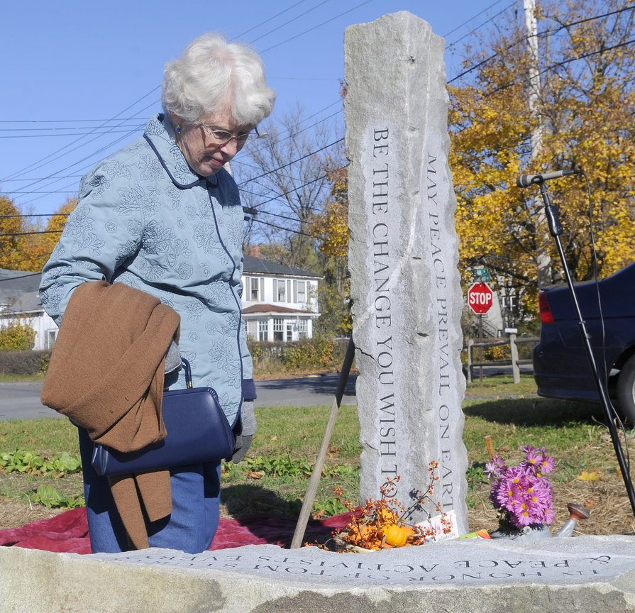 Mary Sturtevant inspects a granite peace pole and bench dedicated in the memory of her late husband, Thomas, on Sunday in Winthrop. A veteran who served in the Navy during the Korean War, Thomas Sturtevant, a former Cony High School teacher, helped found the Maine chapter of Veterans for Peace. The granite peace pole and bench stand in a garden outside the Winthrop Elementary School.