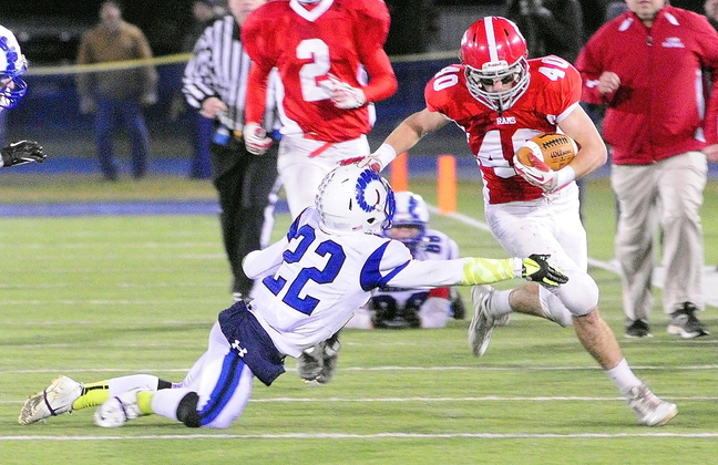 BIG PLAY: Cony wide receiver Jonathan Saban stiff arms Kennebunk defensive back Larson Coppinger while running after catching a pass during the state class B football championship game on Friday at Alfond Stadium in Orono.