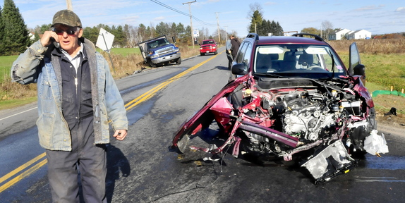 CRASH SCENE: Paul Mushero stands next to an SUV, at right, that struck his truck, in background at left, on Tuesday at the intersection of Route 23 and Rice Rips Road in Oakland.
