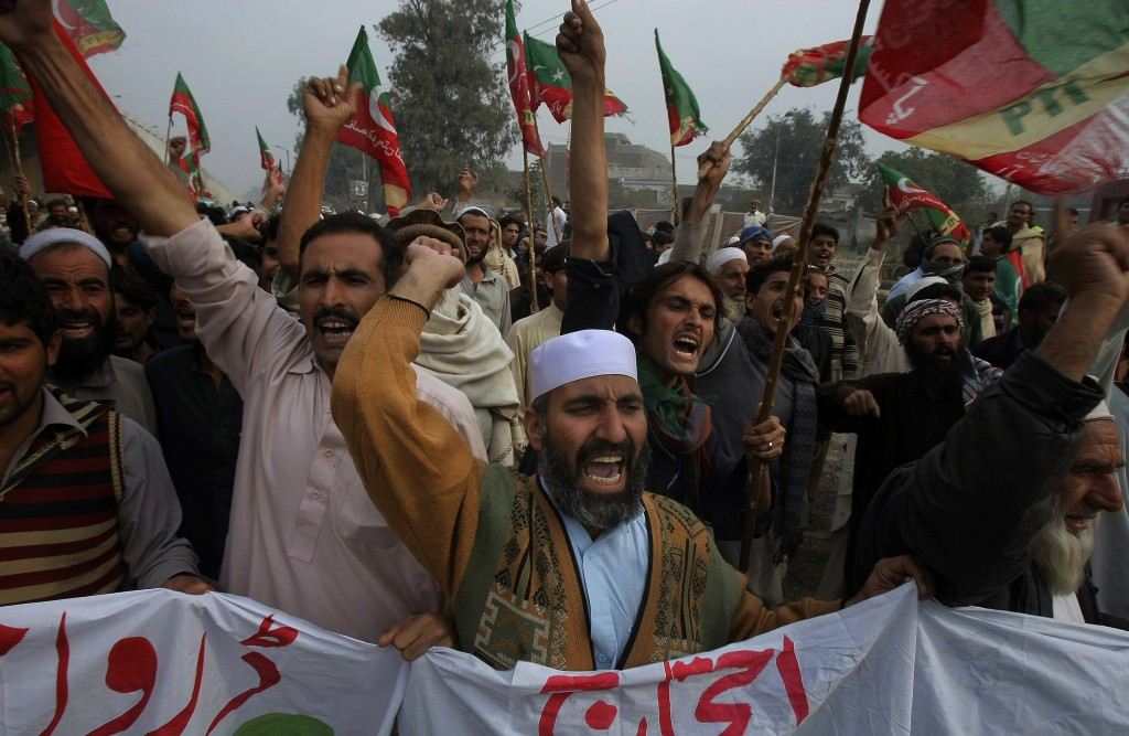 Supporters of Tehreek-e-Insaf or Movement for Justice party chant anti-U.S. slogans during a rally in Peshawar, Pakistan, on Saturday. Thousands of people protesting U.S. drone strikes blocked a road in northwest Pakistan used to truck NATO troop supplies and equipment in and out of Afghanistan, the latest sign of rising tension caused by the attacks.
