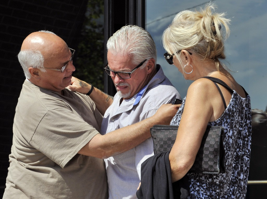 "Steven Davis, brother of slain Debra Davis, center, is comforted by Skip Marcella, left, on Aug. 12, after speaking outside federal court in Boston where a jury found James ""Whitey"" Bulger guilty on several counts of murder, racketeering and conspiracy. Jurors could not agree whether Bulger was involved in Debra Davis' killing. When Bulger is sentenced this week, family members of eight slaying victims are hoping a judge will let them speak, even though Bulger was acquitted in those deaths."