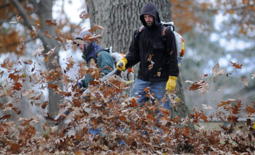 Bureau of General Services employees Tim Campbell, right, and Rik Hutchinson blow oak leaves Tuesday from Capitol Park In Augusta. The men and their colleague, Harold Eames, said working in cool, windy conditions was better than herding leaves on warm, humid days.