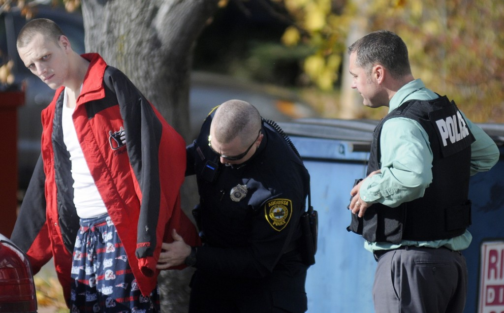 Staff photo by Andy Molloy APPREHEND: Augusta Police arrest Scott Coogan, 28, Wednesday at his home in Augusta on four warrants and charges of burglary, theft, criminal mischief, and violating conditions of release stemming from a burglary of an Augusta business.