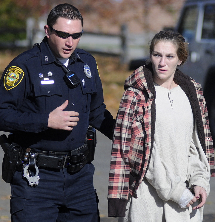 Staff photo by Andy Molloy APPREHEND: Augusta Police Officer Eric Lloyd escorts Gladys Fowler, 31, to a cruiser Wednesday after she was arrested at her Augusta home in connection with a burglary of an Augusta business.
