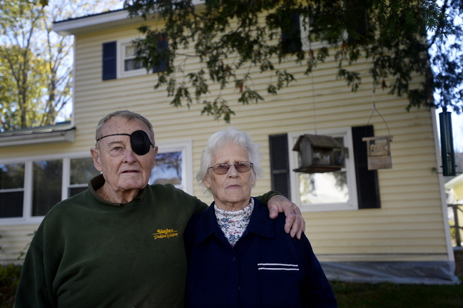 Pauline and Cedric Long stand outside their Camden home Oct. 24. Many people have felt moved by the Longs' story to help the elderly couple, who were financially exploited by their daughter-in-law and son. Gary and Deborah Long got $164,000 that put his parents' home on the line.