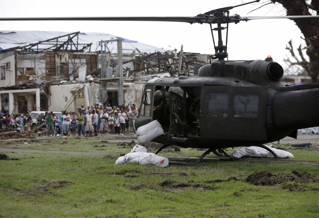 Typhoon survivors watch as a Philippine Air Force helicopter unloads sacks of relief supplies at Tanauan township, Leyte province in central Philippines on Friday, two weeks after Typhoon Haiyan ravaged central Philippines.