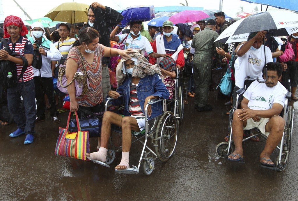 Typhoon Haiyan survivors, some injured, queue up in the rain to board an evacuation flight at the airport in Tacloban, Philippines, on Friday.