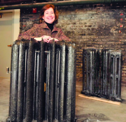 Staff photo by David Leaming NEW USE: Interior designer Lori Larochelle stands between two halves of radiators that were once used for heat in the Gerald Hotel in Fairfield. The units have been restored and will be joined together and a glass top added to make a table for flowers.