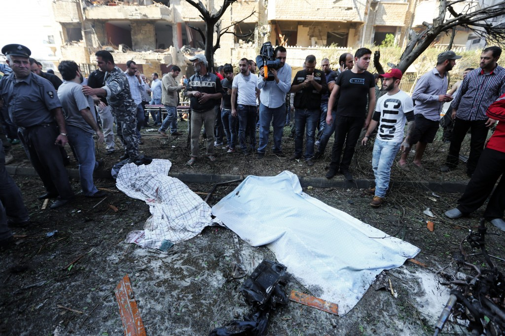 Lebanese people, gather around two dead bodies at the scene where two explosions have struck near the Iranian Embassy killing many, in Beirut, Lebanon, Tuesday, Nov. 19, 2013. The blasts in south Beirut's neighborhood of Janah also caused extensive damage on the nearby buildings and the Iranian mission. The area is a stronghold of the militant Hezbollah group, which is a main ally of Syrian President Bashar Assad in the civil war next door. It's not clear if the blasts are related to Syria's civil war.