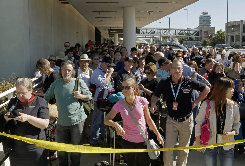 Passengers evacuated from Terminal 1 wait outside Los Angeles International Airport on Friday after shots were fired, prompting authorities to evacuate a terminal and stop flights headed for the city from taking off from other airports.