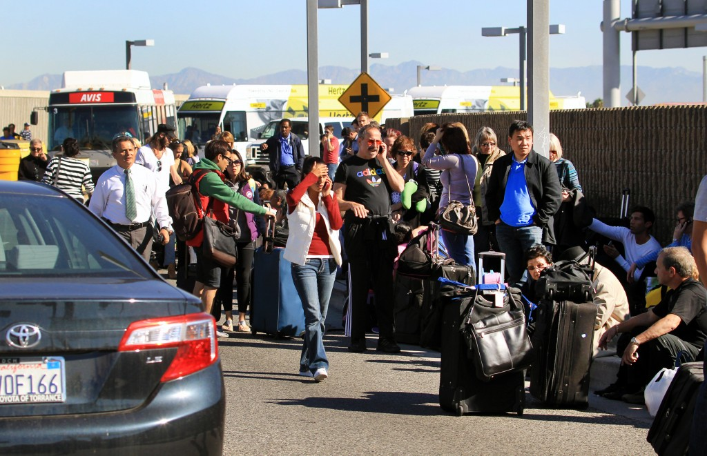 Passengers evacuate the Los Angeles International Airport on Friday after shots were fired there.