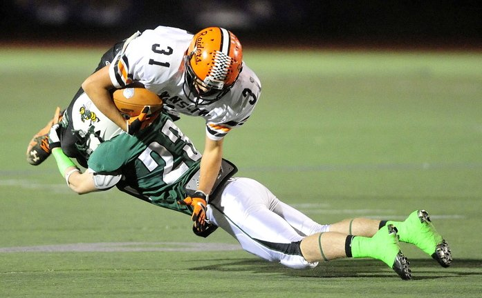 Staff photo by Michael G. Seamans CLASS C FOOTBALL:Leavitt High School's Nate Rousseau, 23, tackles Winslow High School's Richard Crayton, 31, in the second quarter in the Class C state championship game at Fitzpatrick Stadium in Portland on Saturday. Leavitt defeated Winslow 47-18.