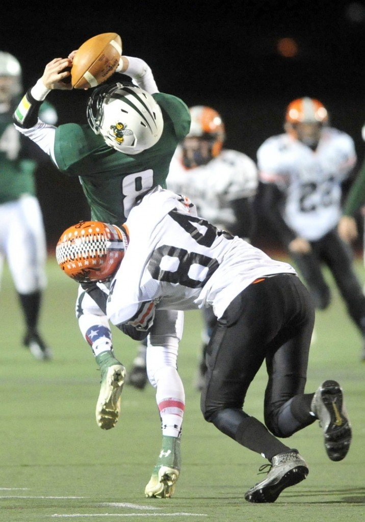 Staff photo by Michael G. Seamans CLASS C FOOTBALL:Winslow High School's Justin Martin, 84, hits Leavitt High School receiver Sam Green, 8, to break up the catch in the second quarter in the Class C state championship game at Fitzpatrick Stadium in Portland on Saturday. Leavitt defeated Winslow 47-18.
