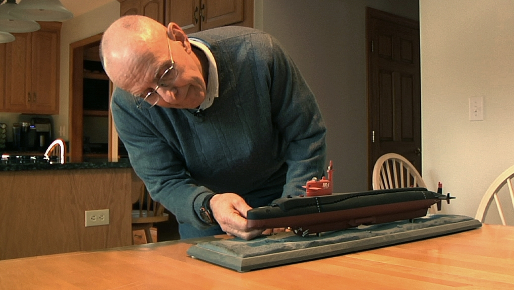 Michael Riegel, a former commander of the U.S. Navy Submarine Base in Groton, Conn., looks at a model of the research submarine NR-1, in his Preston, Conn. home. Now the Navy has collected pieces of the sub for an exhibit at a museum in Groton.