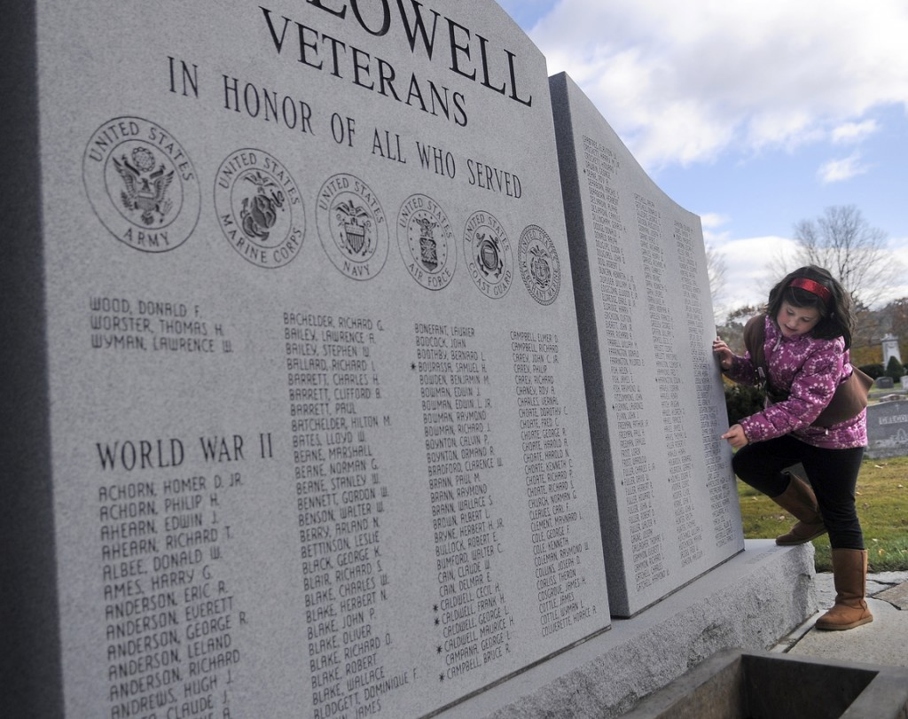 GIVING THANKS: Girl Scout Georgiana Davidson, 7, reads names from the veteran's memorial Monday during a ceremony at the Hallowell Cemetery.