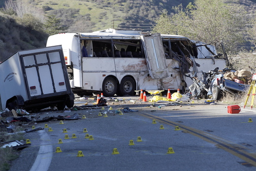 In this Feb. 4, 2013, photo, evidence markers dot the road in front of the wreckage of a tour bus that crashed in the Southern California mountains near San Bernardino. Seven passengers and a pickup truck driver were killed, 11 passengers were seriously injured and 22 others received minor to moderate injuries. The bus driver told passengers the vehicle's brakes had failed.