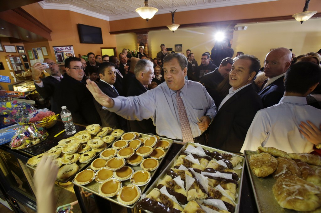 New Jersey Gov. Chris Christie waves to workers at Oasis Pastry Shop during a campaign stop in Hillside, N.J., Monday, Nov. 4, 2013. Christie will face Democratic candidate, Barbara Buono in an election Tuesday, Nov. 5, 2013. (AP Photo/Mel Evans)