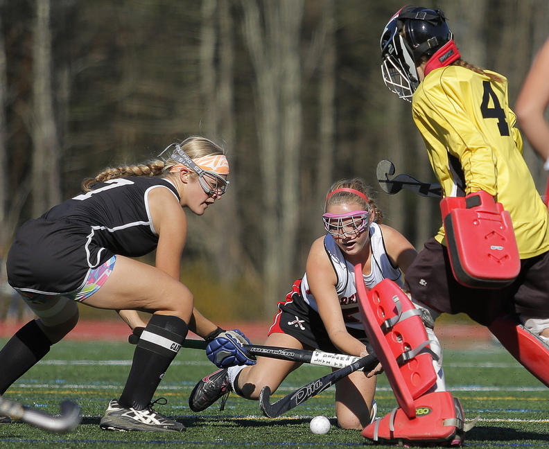 IN CLOSE: Skowhegan's Mikayla Toth, left, battles Scarborough's Ashley Levesque for control of the ball as Skowhegan goalie Leah Kruse gets in on the action during first half play in the Class A field hockey state championship Saturday at Yarmouth High School.