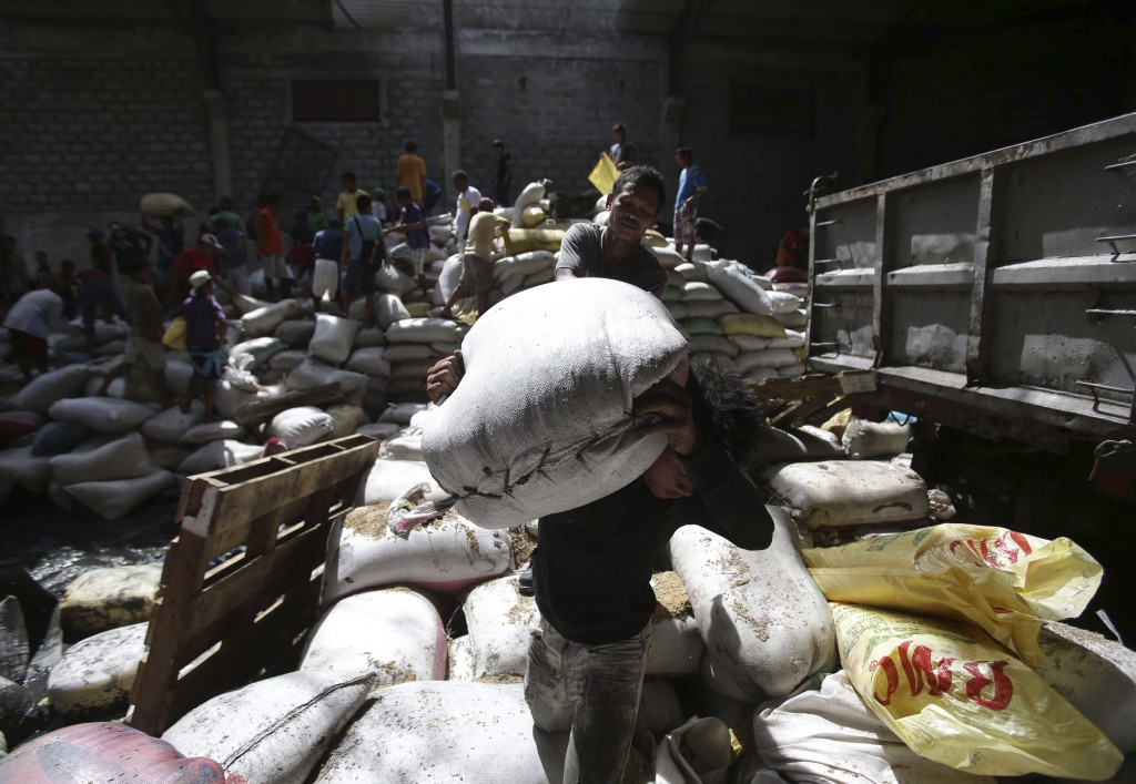 Survivors carry bags of rice from a warehouse that they stormed Monday due to a shortage of food in typhoon-ravaged Tacloban city, in the Philippines. Haiyan slammed the island nation with a storm surge two stories high and some of the highest winds ever measured in a tropical cyclone.