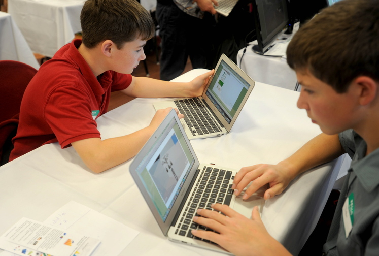 computer skills: Monmouth Middle School students, Trevor Flanagan, 12, left, and Dylan Goff, 14, demonstrate their computer skills during a Kennebec Valley area high school expo at Thomas College on Friday morning. Students and teachers from Kennebec Valley school districts gathered in Waterville to show off their accomplishments.