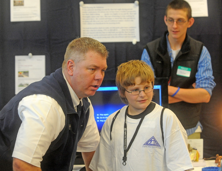 good talk: Peter Gagnon, director of the Capital Area Technical Center in Augusta, speaks with Bodhi Shaw, 12, of Bingham during a Kennebec Valley area high school expo at Thomas College in Waterville on Friday. The schools invited legislators, the governor and other state officials because they want to counteract negative rhetoric about public schools.