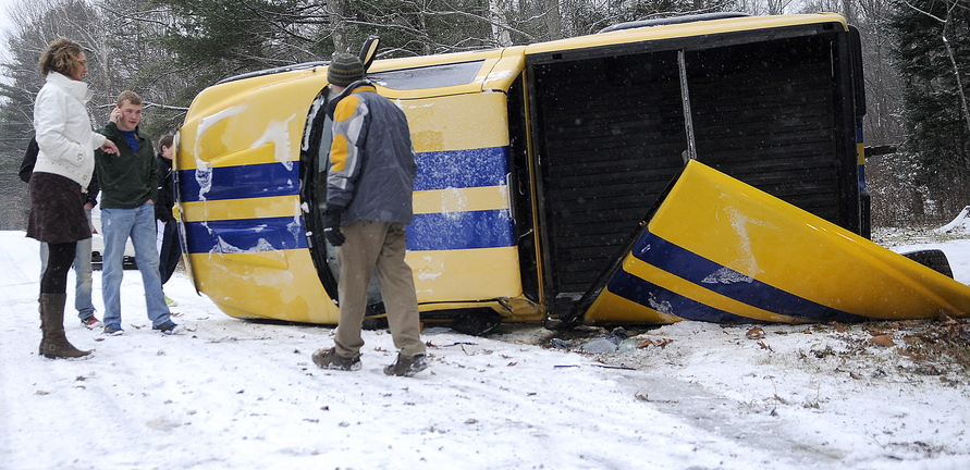 ROLLOVER: Dr. Dean Chamberlain, right, checks on passengers of a pickup that rolled over Tuesday morning on Shady Lane in Hallowell. Several accidents were reported across the state after the first snow to accumulate on roads fell Tuesday morning. Chamberlain, a resident at the Family Medical Institute at MaineGeneral Medical Center, was told nobody was injured in the rollover on slushy roads.