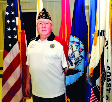 PATRIOT: Ernest Paradis, commander of the Bourque Lanigan Post 5 American Legion in Waterville, stands among flags including the American and the five branches of the armed services.