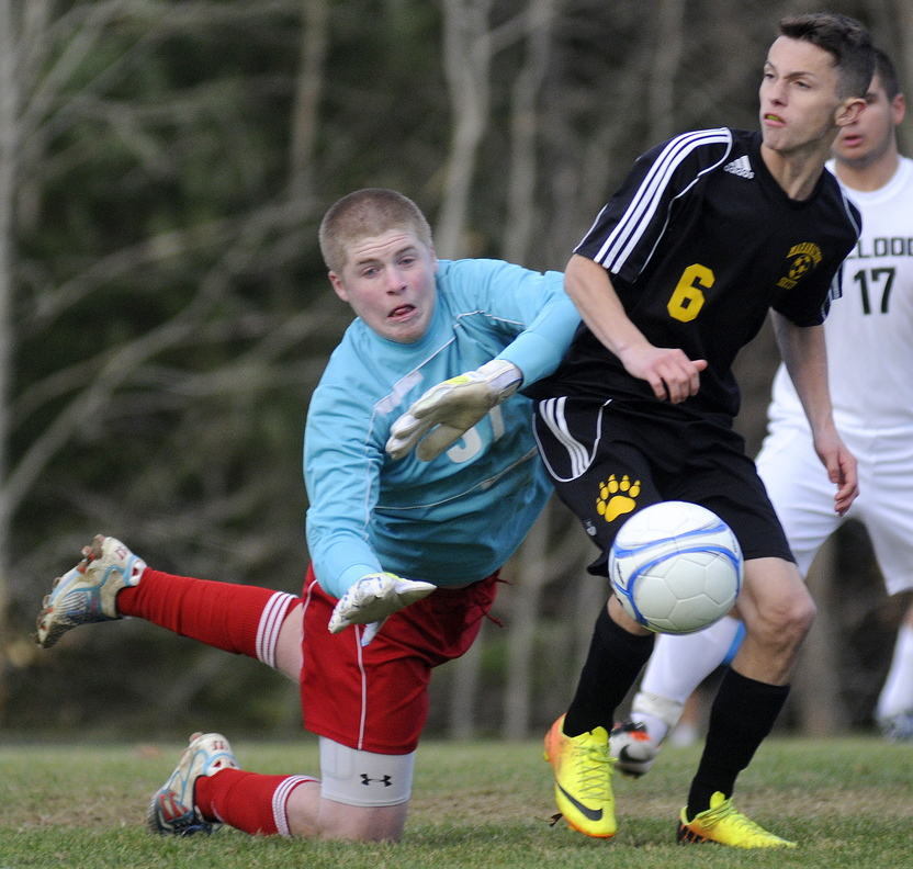Staff photo by Andy Molloy Hall-Dale High School keeper Brian Allen knocks a ball away from Maranacook Community High School's Kodey Solmitz during the Class C Western soccer title game Wednesday in Farmingdale. Maranacook prevailed 1-0.