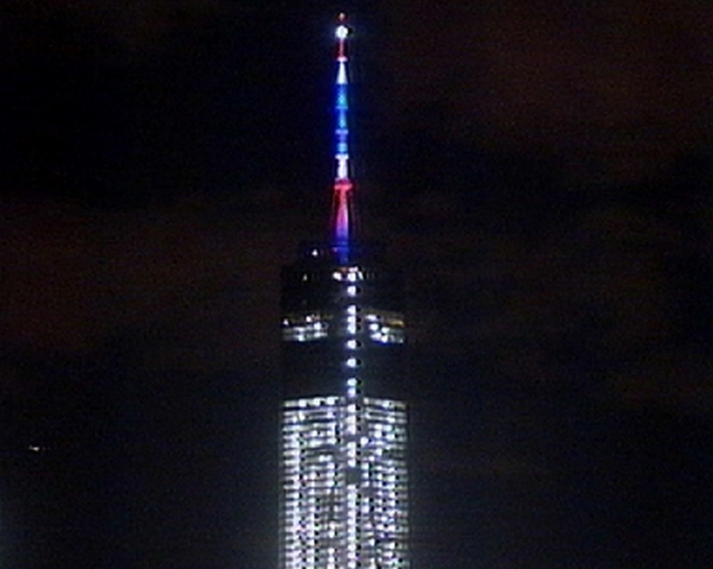 In this image taken from video, colored lights illuminate One World Trade Center as the building conducts its first beacon test last Friday in New York.