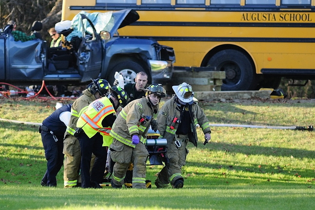 Emergency crews move the pickup truck driver: toward a LifeFlight helicopter at the scene of a crash involving an Augusta school bus and pickup truck Tuesday on Riverside Drive, just south of Stevens Road, in Augusta.