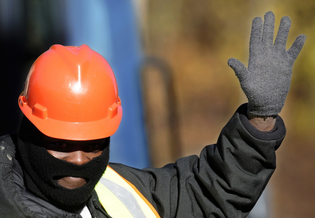 """WARM, THANKS: Clad in a pullover hat and wearing wool gloves, Delaneo Allen waves at a motorist Wednesday while directing traffic while temperatures are in the low 20s F in downtown Augusta. """"I try to be lovable and nice,"""" Allen said of his interaction with the drivers he encounters while flagging, even during a cold snap."""