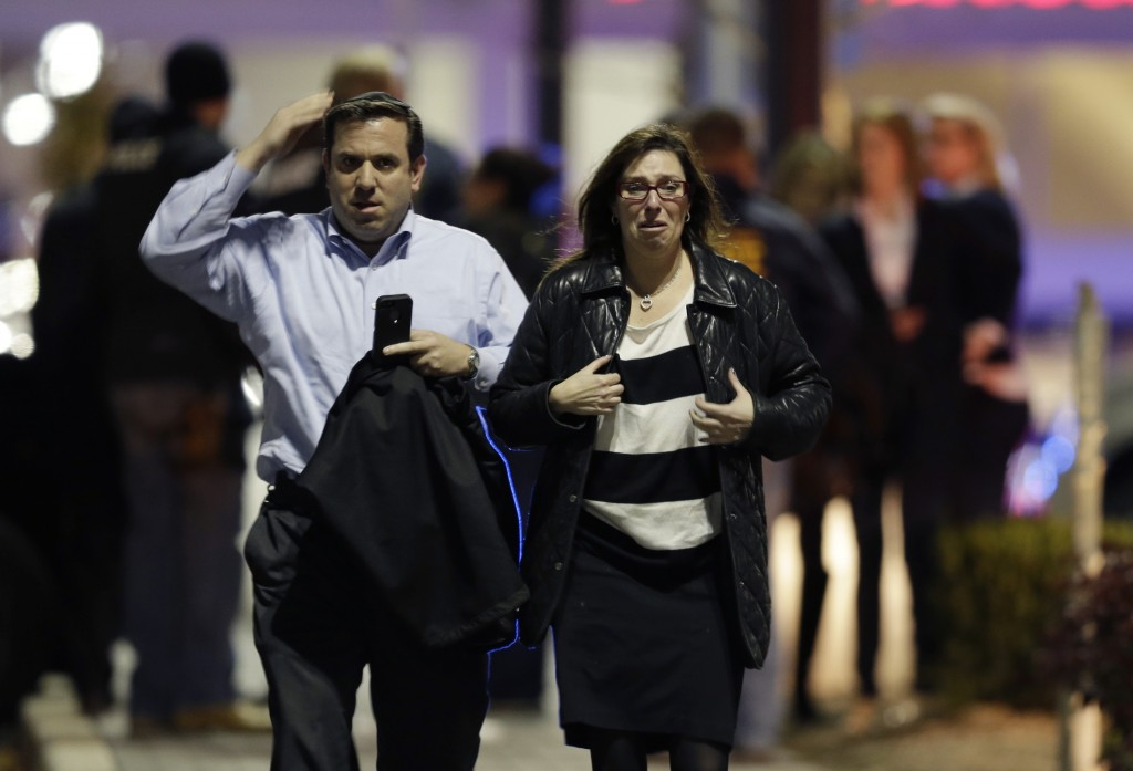 A man and woman leave the Garden State Plaza Mall with officials standing guard behind them Monday night.