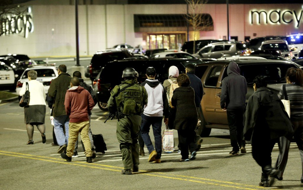 An official wearing tactical gear leads a group of people out of the Garden State Plaza Mall during a lockdown following reports of a shooter, Tuesday in Paramus, N.J.