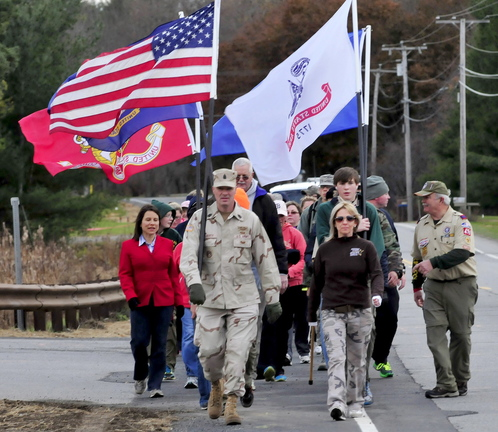 MARCH OF HONOR: Kennebec County Sheriff Randall Liberty leads a group of veterans and supporters as they march through Winslow toward Waterville to take part in the Veterans Day parade on Monday, Nov. 11, 2013. At right is his wife Jodi. Kennebec District Attorney Maeghan Maloney is at left.